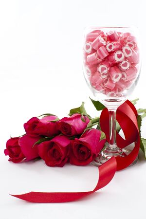 Valentine Series, Candy in wine glass with rose on white background photo