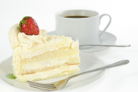 Delicious vanilla cake with strawberry decorate on top and a cup of coffee photo