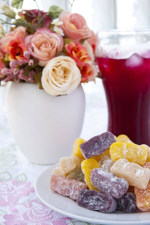 Colorful fruit jelly candy on white plate with juice photo