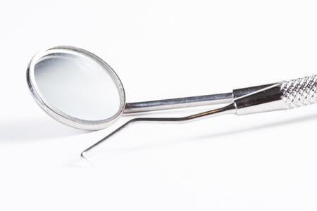 test probe: Due strumenti dentali: specchio dentale e sonda su sfondo bianco Archivio Fotografico