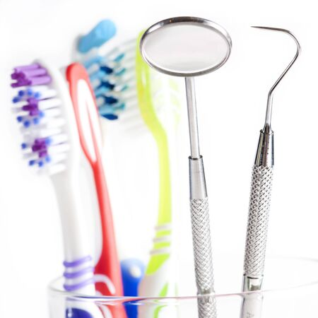Toothbrush and Dental mirror - explorer in glass on white background  photo