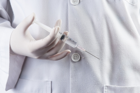 Doctor / Nurse holding a syringe ready an injection