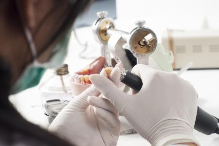 Dental technician working with articulator in dental laboratory  Archivio Fotografico