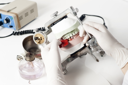 Dental technician working with articulator in dental laboratory  Banco de Imagens