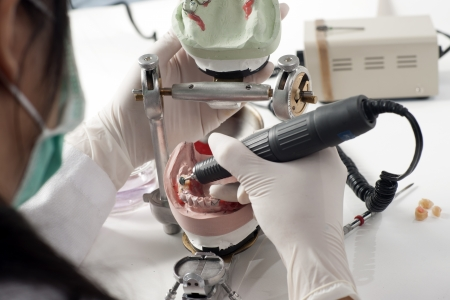 Dental technician working with articulator in dental laboratory  Stock Photo