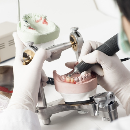 Dental technician working with articulator in dental laboratory  Imagens