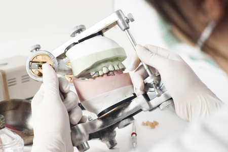 Dental technician working with articulator in dental laboratory  Stok Fotoğraf