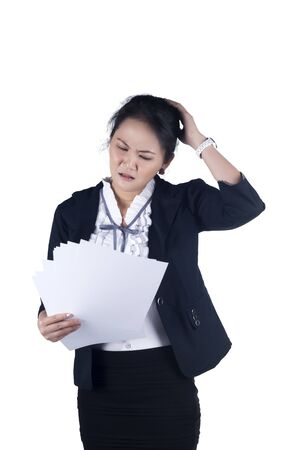 Unhappiness and stress business woman reading reports  Isolated white background  Model is Asian woman  Stock Photo - 16593381