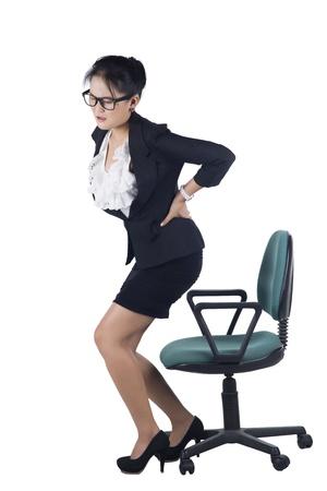 Mulher de negócio com dor nas costas depois de um longo trabalho na cadeira. Isolado no fundo branco, modelo é mulher asiática.