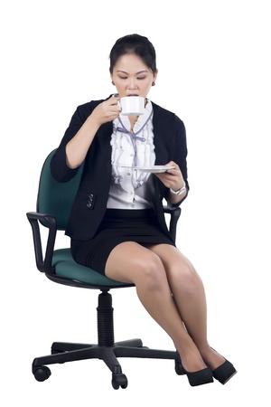 mujer sentada: Mujer de negocios sentado en silla de oficina con una taza de café, aislado en blanco. Modelo es mujer asiática.