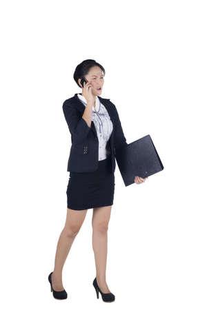 Cara enojada de la mujer de negocios caminando hablando por tel�fono m�vil y la carpeta de tenencia, aislados en fondo blanco. Modelo es mujer asi�tica. photo