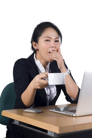 Young business woman yawning at her desk with a cup of coffee, Model is Asian woman. Stock Photo - 17158052