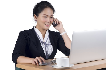 Portrait of business woman speaking on mobile phone while using laptop in office, Isolated white background. Model is Asian woman.   Banco de Imagens