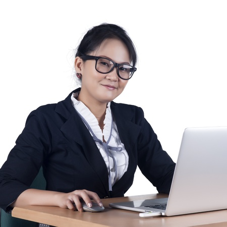 Portrait of confident business woman sitting at the table and working on the laptop, Isolated on white background. Model is Asian woman.