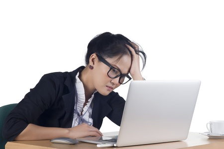 Bored business woman working on laptop looking very boring at the computer, Isolated white background. Model is Asian woman.