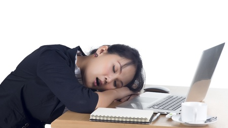 Tired business woman sleeping at her desk. Isolated on white background. Model is Asian woman. photo