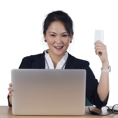 Happy woman shopping online paying with credit card - Isolated on white background. Model is Asian woman. photo