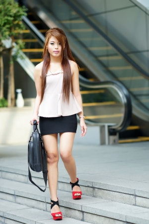 Young business woman have notebook bag and walking in front of escalator outdoor. Model is Asian woman. photo