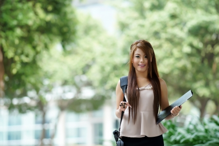 Young woman in business attire, carrying briefcase and holding folder standing outside. photo