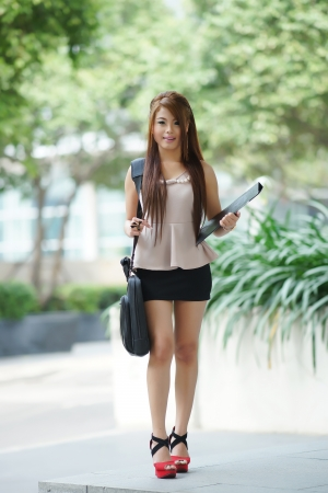 Young woman in business attire, carrying briefcase and holding folder standing outside. Stock Photo