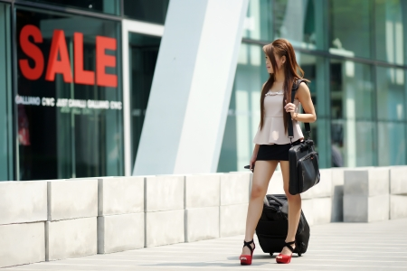 Young business woman walking outside of shopping plaza with her rolling luggage and briefcase. (shallow DOF)