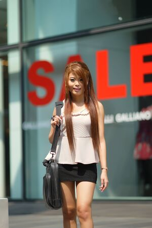 Young business woman walking outside of shopping plaza with her briefcase. (shallow DOF) photo