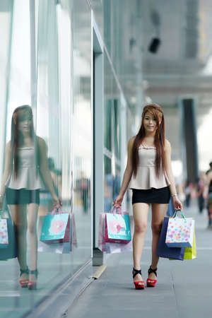 Beautiful young woman shows an ecstatic expression while holding shopping bags outside shopping mall. photo