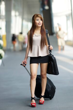 Young business woman walking outside of shopping plaza with her rolling luggage and briefcase. (shallow DOF) photo