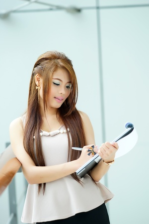 Portrait of young business woman standing near window in modern office and writing notes  photo