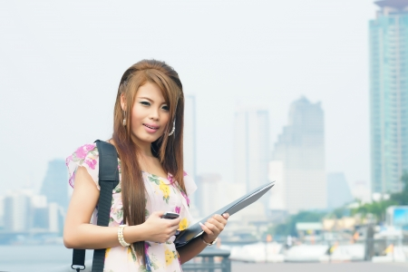 Beautiful business woman walking outside her office. Portrait of asian.  photo