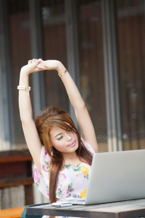 Young attractive business woman tired and stretching on her laptop at outdoors cafe. Archivio Fotografico
