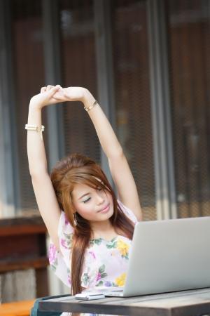 estiramientos: Joven mujer de negocios atractivo cansado y se extiende en su computadora port�til en el caf� al aire libre.