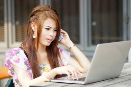 Young attractive business woman working on her laptop at outdoors cafe, She look very bored and stressed.  photo
