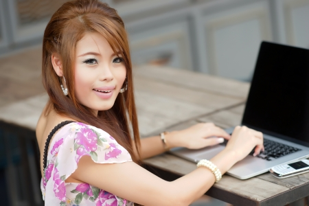 Young attractive business woman working on her laptop at outdoors cafe photo
