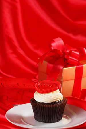 Cupcake with a red heart on top and gifts in boxes on red satin background photo