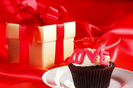 Cupcake with a red rose on top and gifts in boxes on red satin background photo