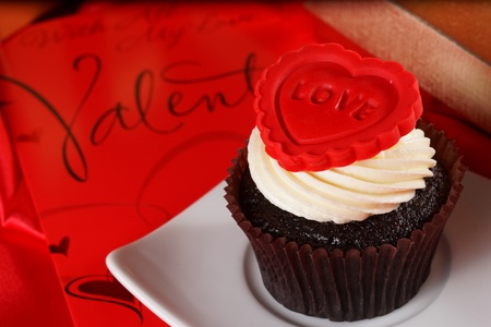 Cupcake with a red heart on top and gifts in boxes on red satin background Stock Photo - 18013099