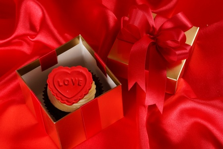 Cupcake with a red heart on top in gifts boxes on red satin background photo