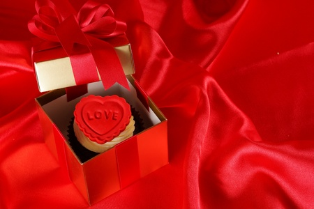 Cupcake with a red heart on top in gifts boxes on red satin background Stock Photo - 18013132