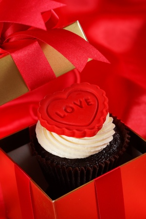 Cupcake with a red heart on top in gifts boxes on red satin background Stock Photo - 18013054