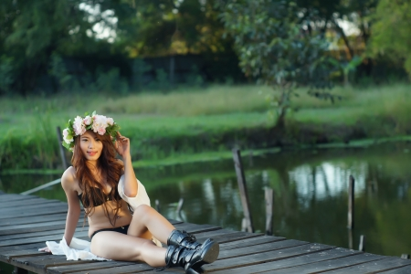 Young sexy Asian woman in black lingerie sitting on the wooden bridge outdoor. photo
