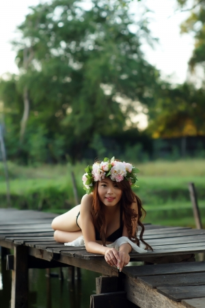 Young sexy Asian woman in black lingerie lying on the wooden bridge outdoor. photo