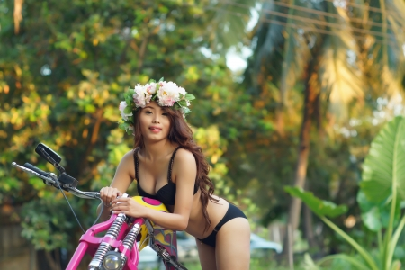 Young sexy Asian woman in black lingerie on pink motorcycle. photo