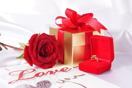 Gouden diamanten ring met geschenkdoos en rode roos op met satijn achtergrond