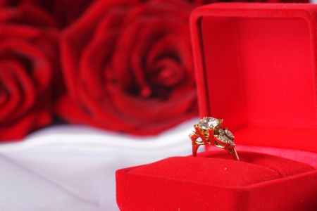 Golden diamond ring in box and red rose on white satin background photo