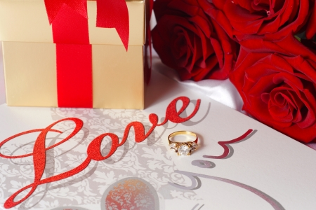 Golden diamond ring with gift box and red rose on with satin background