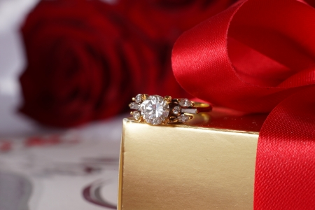 Golden diamond ring with gift box and red rose on with satin background photo