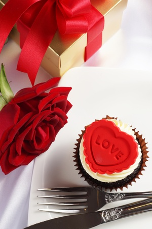 Valentine cupcake with red rose and gift box on white satin background photo