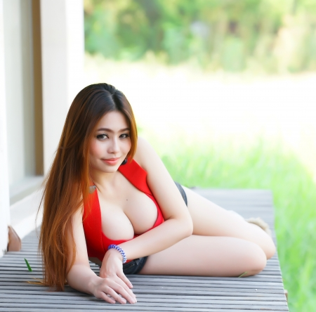 Young beautiful Asian woman in red lingerie voluptuous posing outdoors