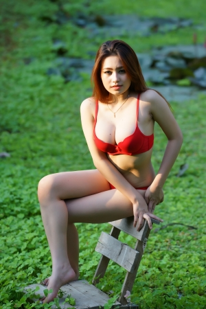 Young beautiful Asian woman in red lingerie voluptuous posing in pond full weeds. photo